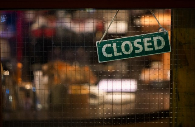 A closed sign hanging in a shop window.