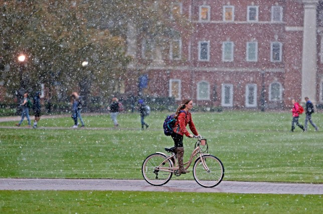 Students make their way through campus as snow flies through the air