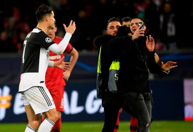 Cristiano Ronaldo tries to confront a pitch invader who grabbed him by the neck