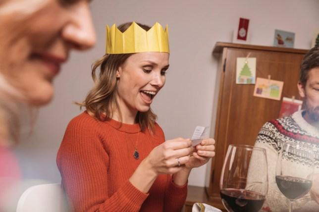 Woman opening a joke from a Christmas Cracker