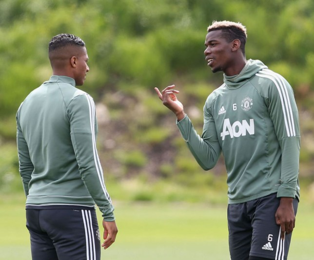 Antonio Valencia and Paul Pogba chat during Manchester United training