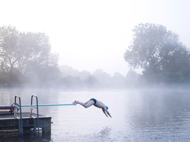 Man diving off board in outdoor lake