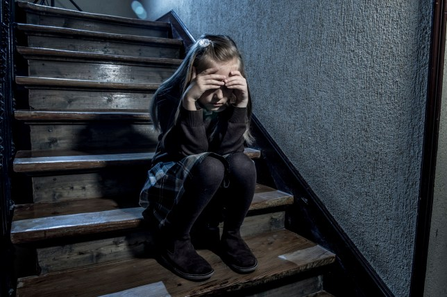 7 or 8 years old sad depressed and worried schoolgirl sitting on staircase desperate and scared suffering bullying and harassment at school in dramatic lighting and bullied children concept