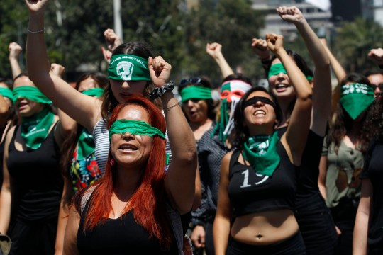 """SANTIAGO, CHILE - DECEMBER 06: Demonstrators wearing green handkerchiefs covering their eyes sing and dance in a feminist flash mob performing """"Rapist in Your Path"""" (In Spanish: Un violador en tu camino) in protest of violence against women on December 6, 2019 in Santiago, Chile. The song, written by local feminist group Lastesis is becoming an international feminist phenomenon. (Photo by Marcelo Hernandez/Getty Images) *** BESTPIX ***"""