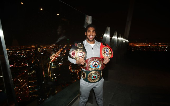 Heavyweight boxer Anthony Joshua poses for photographers with his WBA, IBF, WBO and IBO championship belts