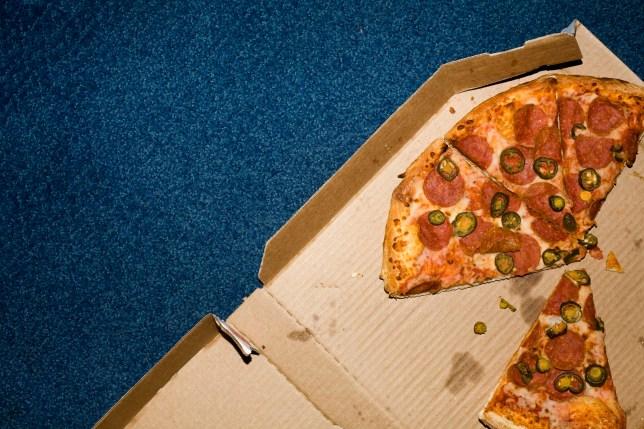 Open pizza box on a blue carpet. Los Angeles, California, USA