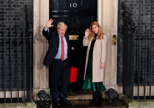Britain's Prime Minister Boris Johnson and his girlfriend Carrie Symonds wave as they arrive at 10 Downing Street on the morning after the general election in London, Britain, December 13, 2019. REUTERS/Thomas Mukoya