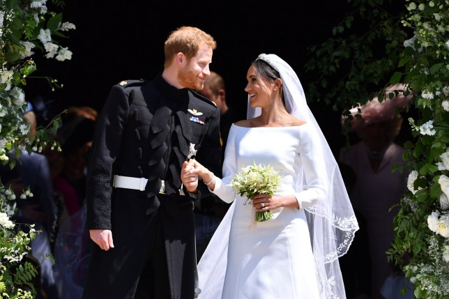TOPSHOT - Britain's Prince Harry, Duke of Sussex and his wife Meghan, Duchess of Sussex emerge from the West Door of St George's Chapel, Windsor Castle, in Windsor, on May 19, 2018 after their wedding ceremony. (Photo by Ben STANSALL / various sources / AFP) (Photo credit should read BEN STANSALL/AFP via Getty Images)