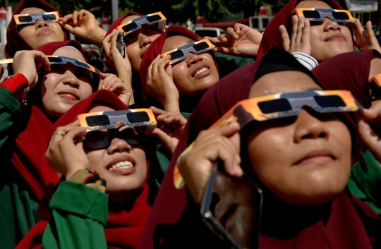 Women wearing special protective glasses observe the annular solar eclipse at mosque in Gowa, South Sulawesi, Indonesia December 26, 2019 in this photo taken by Antara Foto. Antara Foto/Abriawan Abhe/via REUTERS ATTENTION EDITORS - THIS IMAGE WAS PROVIDED BY A THIRD PARTY. MANDATORY CREDIT. INDONESIA OUT. TPX IMAGES OF THE DAY
