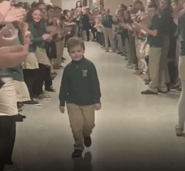 Grab of six year-old John Oliver Zippay walking down his school corridor as classmates cheer him on