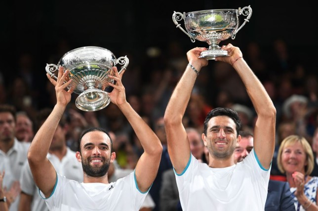 Colombia's Juan Sebastian Cabal (L) and Colombia's Robert Farah (R) pose with the trophy after beating France's Nicolas Mahut and France's Edouard Roger-Vasselin to win the men's doubles final on day twelve of the 2019 Wimbledon Championships at The All England Lawn Tennis Club in Wimbledon, southwest London, on July 13, 2019.
