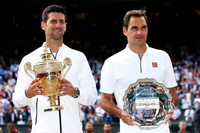 Novak Djokovic stands alongside Roger Federer after winning Wimbledon