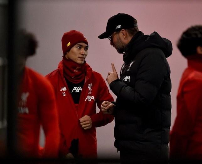 Jurgen Klopp speaks to Takumi Minamino during Liverpool training
