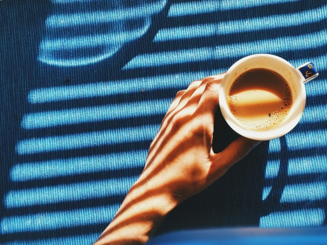 Hand and coffee cup