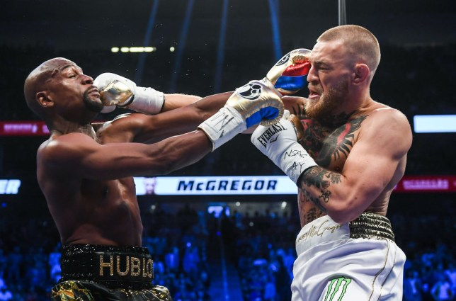Conor McGregor and Floyd Mayweather punch each other during their boxing match