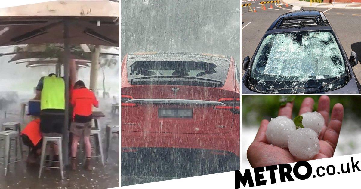 Workers dive under umbrella to avoid massive hailstones