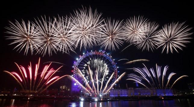 Fireworks explode over the London Eye Ferris wheel by the River Thames