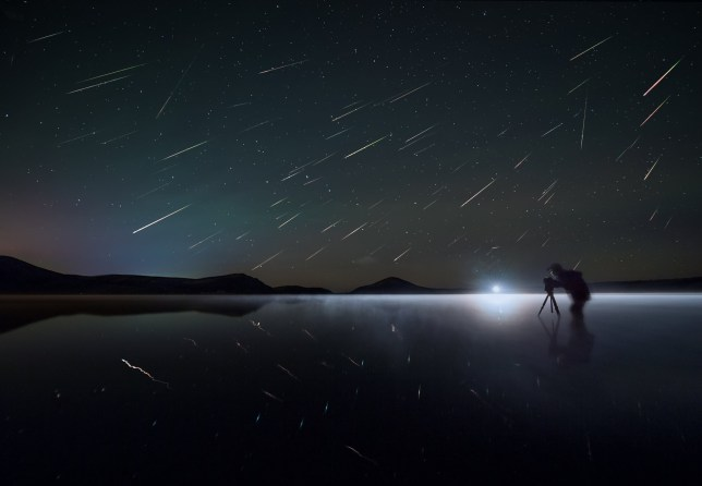 A photographer outside at night with dozens of shooting stars in the night sky