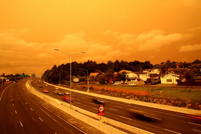 AUCKLAND, NEW ZEALAND - JANUARY 05: Cars travel with their lights on as tobacco coloured skies over Auckland block out the sun on January 05, 2020 in Auckland, New Zealand. The smoke has travelled from Australia, where hundreds of fires continue to burn across New South Wales, Victoria and South Australia, with the Australian Defence Force now called in to help with firefighting and rescue efforts. 14 people have died in the fires in NSW, Victoria and SA since New Year's Eve. (Photo by Phil Walter/Getty Images)