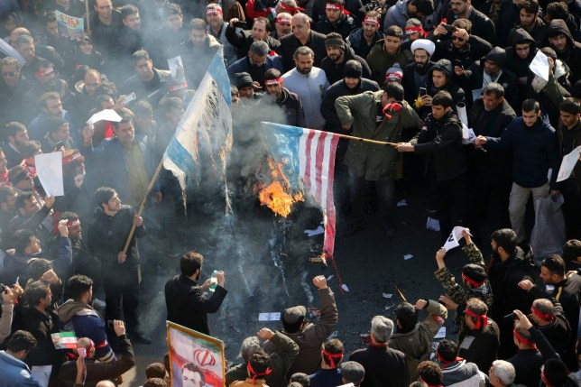 Iranians set a US and an Israeli flag on fire during a funeral procession organised to mourn the slain military commander Qasem Soleimani, Iraqi paramilitary chief Abu Mahdi al-Muhandis and other victims of a US attack in the capital Tehran on January 6, 2020. - Mourners packed the streets of Tehran for ceremonies to pay homage to Soleimani, who spearheaded Iran's Middle East operations as commander of the Revolutionary Guards' Quds Force and was killed in a US drone strike on January 3 near Baghdad airport. (Photo by Atta KENARE / AFP) (Photo by ATTA KENARE/AFP via Getty Images)