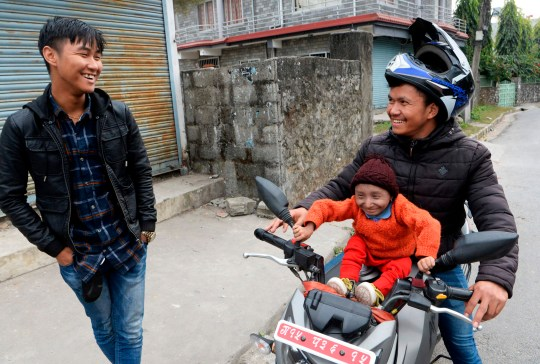 In this photograph taken on December 8, 2018, Khagendra Thapa Magar, the world's shortest man, sits on the tank of his younger brother Maheshl Thapa Magar bike's in front of their house in Pokhara, some 200 kms west of Kathmandu. - The world's shortest man who could walk, as verified by Guinness World Records, died on Janaury 17, 2020 at a hospital in Nepal, his family said. Khagendra Thapa Magar, who measured 67.08 centimetres (2 feet 2.41 inches), died of pneumonia at a hospital in Pokhara, 200 kilometres from Kathmandu, where he lived with his parents. (Photo by PRAKASH MATHEMA / AFP) (Photo by PRAKASH MATHEMA/AFP via Getty Images)