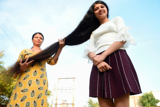 Nilanshi Patel, 17, who has been awarded the 2019 Guinness World Record for the longest hair in the teenager category, 190 cm, poses for a picture with her mother Kaminibenat at Modasa town, some 110 Kms from Ahmedabad on January 19, 2020. - Patel has been awarded the 2019 Guinness World Record for the longest hair at 190 cm in the teenager category. In 2018 she bagged Guinness World Record in the same category at 170,5 cm. (Photo by SAM PANTHAKY / AFP) (Photo by SAM PANTHAKY/AFP via Getty Images)