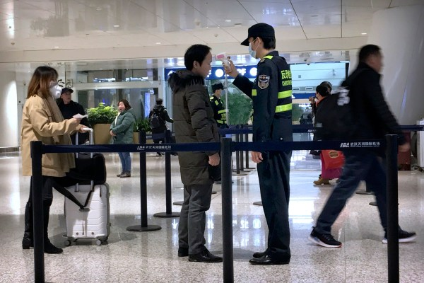 An official uses an infrared thermometer on a traveler at a health screening checkpoint at Wuhan Tianhe International Airport in Wuhan in southern China's Hubei province, Tuesday, Jan. 21, 2020. A fourth person has died in an outbreak of a new coronavirus in China, authorities said Tuesday, as more places stepped up medical screening of travelers from the country as it enters its busiest travel period. (AP Photo/Emily Wang)