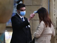 A staff member checks the temperature of a guest entering the New Orient Landmark hotel in Macau on January 22, 2020, after the former Portuguese colony reported its first case of the new SARS-like virus that originated from Wuhan in China. - Macau on January 22 reported its first confirmed case of the new SARS-like coronavirus as authorities announced all staff in the city's bustling casinos had been ordered to wear face masks. (Photo by Anthony WALLACE / AFP) (Photo by ANTHONY WALLACE/AFP via Getty Images)