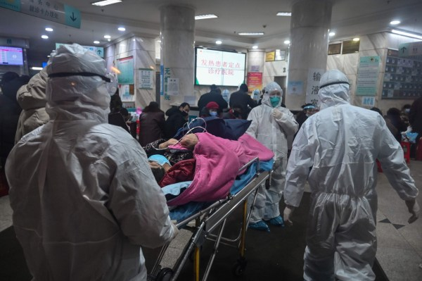 In this photo taken on January 25, 2020, medical staff wearing protective clothing to protect against a previously unknown coronavirus arrive with a patient at the Wuhan Red Cross Hospital in Wuhan. - The number of confirmed deaths from a viral outbreak in China has risen to 54, with authorities in hard-hit Hubei province on January 26 reporting 13 more fatalities and 323 new cases. (Photo by Hector RETAMAL / AFP) (Photo by HECTOR RETAMAL/AFP via Getty Images)