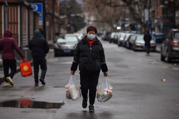 TOPSHOT - A woman wearing a protective facemask returns from a market in Wuhan on January 26, 2020, a city at the epicentre of a viral outbreak that has killed at least 56 people and infected nearly 2,000. - China on January 26 expanded drastic travel restrictions to contain the viral contagion, as the United States and France prepared to evacuate their citizens from the quarantined city at the outbreak's epicentre. (Photo by Hector RETAMAL / AFP) (Photo by HECTOR RETAMAL/AFP via Getty Images)