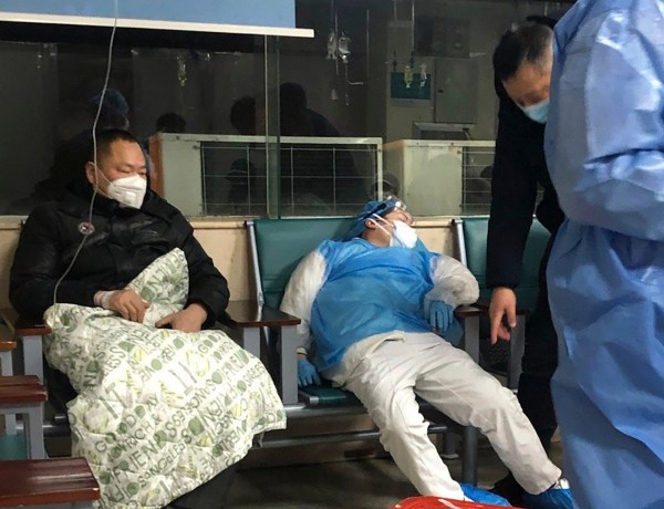 In this Jan. 23, 2020, photo, a medical worker rests in a chair next to a patient at a hospital in Wuhan in central China's Hubei Province. As Beijing instates one of the largest quarantines in modern history, locking down over 50 million people in Hubei province, questions are swirling around the provincial government's sluggish initial response. (AP Photo)