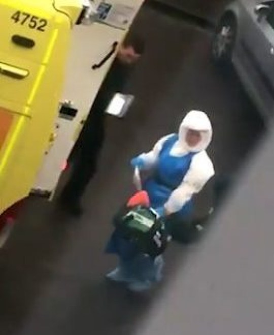 Hazmat wearing paramedics load a patient into the back of an ambulance in Birmingham amid fears coronavirus has spread to the UK. Video circulating on social media shows a man dawning a face mask and a black hoodie being escorted out of a home on a residential street in Harborne. A paramedic head-to-toe in protective gear, including a white hazmat suit, blue apron, gloves and a mask with a visor, then follows him into the ambulance. / Source: MOL