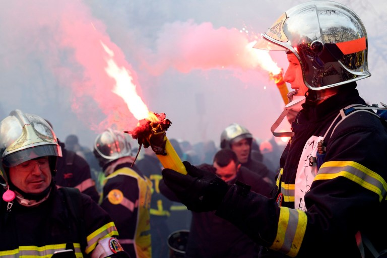Firefighters brandish flares as they take part in a demonstration to protest against French government's plan to overhaul the country's retirement system in Paris, on January 28, 2020. (Photo by Bertrand GUAY / AFP) (Photo by BERTRAND GUAY/AFP via Getty Images)