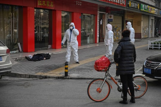 This photo taken on January 30, 2020 shows officials in protective suits checking on an elderly man (L) wearing a facemask who collapsed and died on a street near a hospital in Wuhan. - AFP journalists saw the body on January 30, not long before an emergency vehicle arrived carrying police and medical staff in full-body protective suits. The World Health Organization declared a global emergency over the new coronavirus, as China reported on January 31 the death toll had climbed to 213 with nearly 10,000 infections. (Photo by Hector RETAMAL / AFP) / TO GO WITH China-health-virus-death,SCENE by Leo RAMIREZ and Sebastien RICCI (Photo by HECTOR RETAMAL/AFP via Getty Images)
