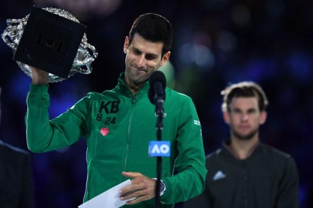 Novak Djokovic lifts the Australian Open title aloft after beating Dominic Thiem