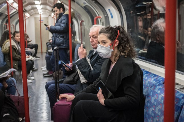 Woman wearing face mask against coronavirus on tube