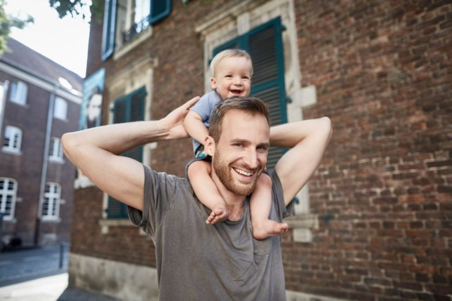 Smiling father carrying baby on shoulders