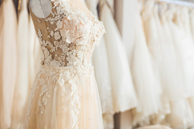 A wedding dress on a mannequin, with other wedding dresses hanging in the background
