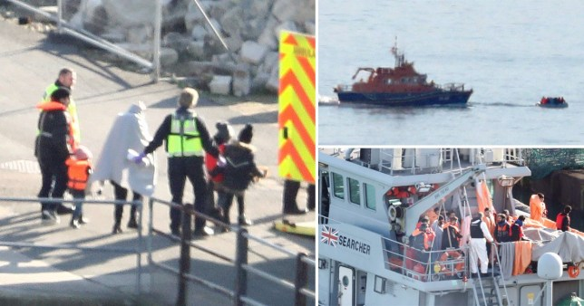 Migrants are led to an ambulance as they are brought ashore in Dover today