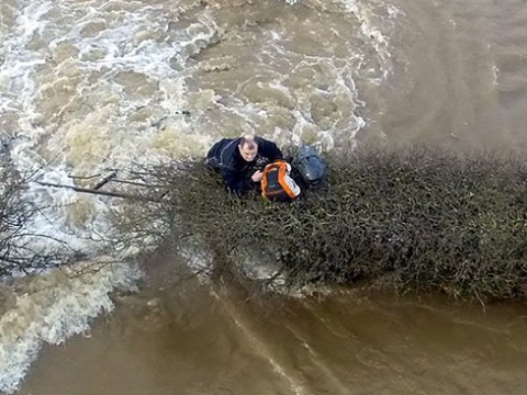 Biker who tried to get through floods clings to fence as he awaits rescue