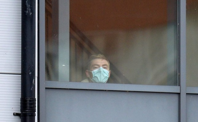 A person wearing a face mask looks out from a window of the accommodation block at Arrowe Park Hospital in Wirral, Britain, February 2, 2020. REUTERS/Peter Powell