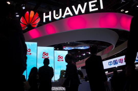 Attendees walk past a display for 5G services from Chinese technology firm Huawei at the PT Expo in Beijing. (Credits: AP)