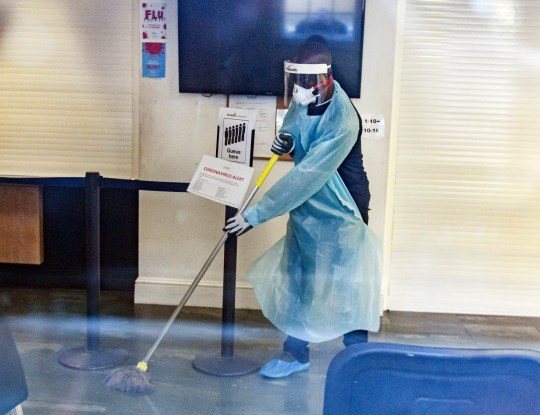 ? Licensed to London News Pictures. 02/13/2020. London, UK. A man with a medical mask cleaning the surfaces inside the Ritchie Street health center in Islington, closed due to the Coronavirus COVID-19 epidemic, according to a notice on his website. Photo credit: Ben Cawthra / LNP