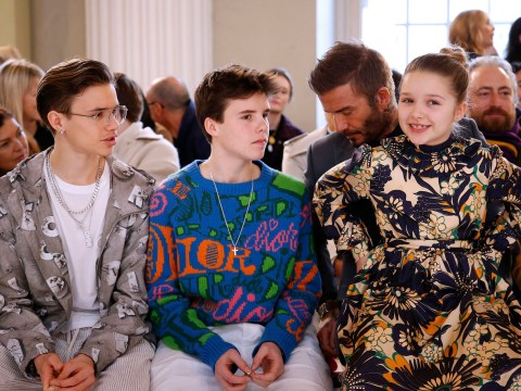 Harper Beckham sits on David's lap as she proudly watches Victoria's fashion show with brothers