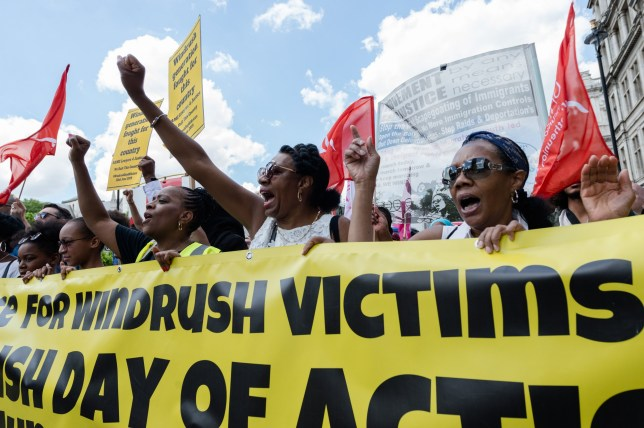 A group of protesters march across Westminster Bridge to mark the first official Windrush Day with a demonstration demanding justice for members of the Windrush Generation on 22 June, 2019 in London, England. The Windrush Day of Action, taking place simultaneously in seven cities across the UK, is part of an ongoing campaign against the impact of Government's 'hostile environment' immigration policies and deportations from the UK to the Caribbean. Demonstrators call for a formal UN investigation into the Windrush scandal, an end to deportations and guarantee of full rights and compensations towards those affected by the scandal. (Photo by WIktor Szymanowicz/NurPhoto via Getty Images)