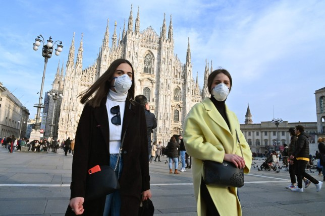 TOPSHOT - Woen wearing a respiratory mask walk across Piazza del Duomo in central Milan on February 23, 2020. - Tens of thousands of Italians prepared for a weeks-long quarantine in the country's north on February 23 as nerves began to fray among the locals faced with new lockdown measures. (Photo by ANDREAS SOLARO / AFP) (Photo by ANDREAS SOLARO/AFP via Getty Images)