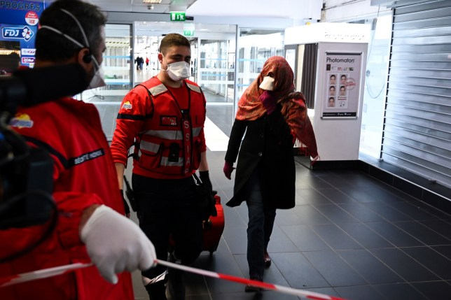 A woman wearing a protective facemask is evacuated from the security zone where a bus comming from Milan is blocked at the train and bus station Lyon Perrache, due to suspected COVID-19 the novel coronavirus on board, in Lyon, on February 24, 2020. (Photo by JEAN-PHILIPPE KSIAZEK / AFP) (Photo by JEAN-PHILIPPE KSIAZEK/AFP via Getty Images)