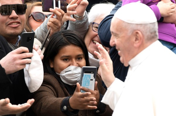 epa08248480 Pope Francis greets the faithful, many of whom are wearing medical face masks due to the ongoing coronavirus outbreak in Italy, during his weekly General Audience in St. Peter's Square at the Vatican, 26 February 2020. EPA/MAURIZIO BRAMBATTI