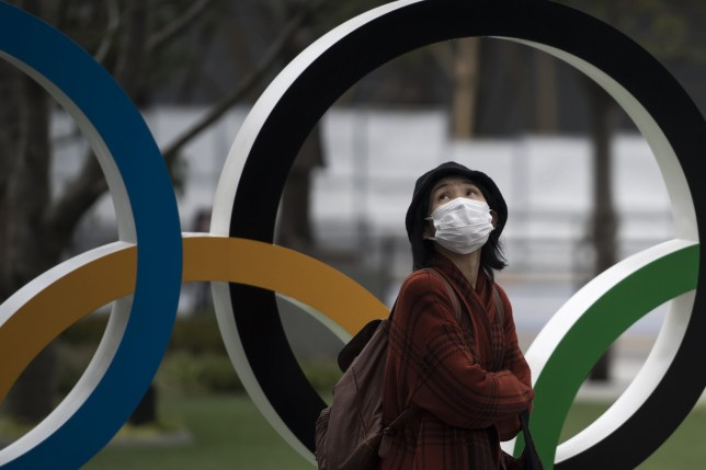 TOKYO, JAPAN - FEBRUARY 26: A woman wearing a face mask walks past the Olympic rings in front of the new National Stadium, the main stadium for the upcoming Tokyo 2020 Olympic and Paralympic Games, on February 26, 2020 in Tokyo, Japan. Concerns that the Tokyo Olympics may be postponed or cancelled are increasing as Japan confirms 862 cases of Coronavirus (COVID-19) and as some professional sporting contests are being called off or rescheduled and some major Japanese corporations ask for people to work from home. (Photo by Tomohiro Ohsumi/Getty Images)