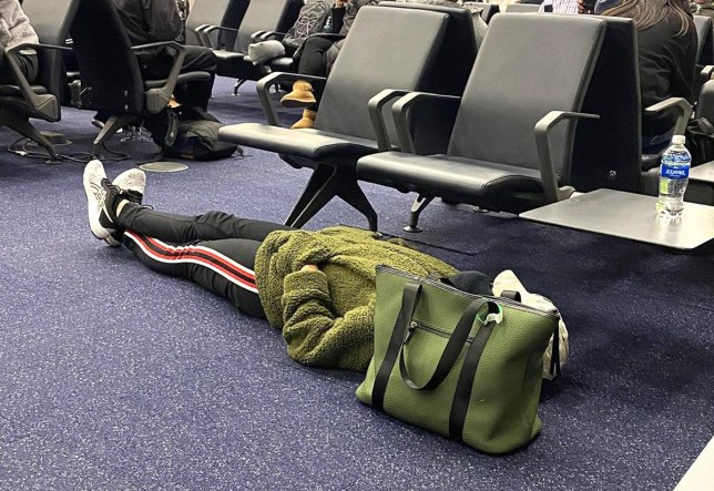 woman sleeping on the floor of an airport, wearing a green jacket(Picture: Traveling Creeps/Instagram)